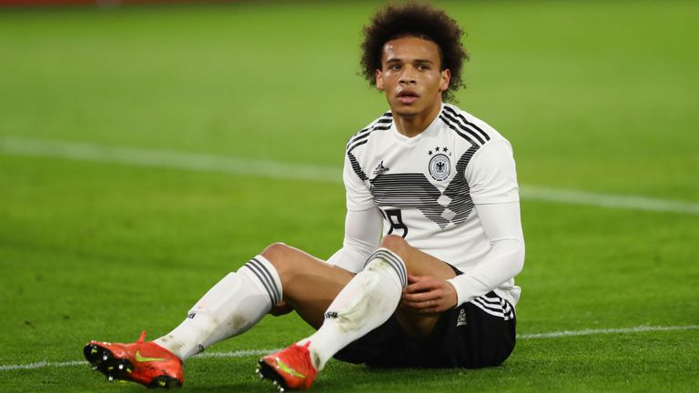 Leroy sane german professional football player sitting on ground after injury